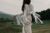 a boho lace sheath wedding dress with long sleeves and long fringe that makes the gown look super trendy