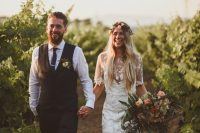 a boho lace sheath wedding dress with short sleeves, a high neckline and long fringe over the skirt
