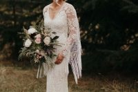 a boho lace sheath wedding gown with a V-neckline, a train and fringe on the sleeves