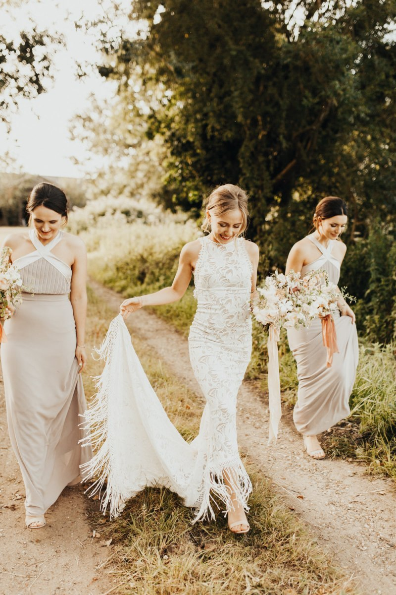 a boho lace sheath wedding gown with a halter neckline and a high low skirt with fringe is super bold