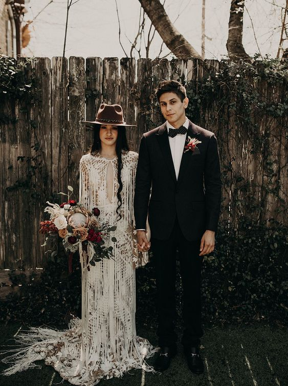 a boho lace sheath wedding gown with a plunging neckline, a train and long fringe plus a brown hat