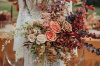 a bold fall ombre wedding bouquet from white to deep purple, with blush, mauve, pink and burgundy blooms and dried greenery