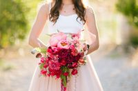 a bold light pink to red and burgundy plus greenery wedding bouquet with shiny ribbons is a fantastic statement