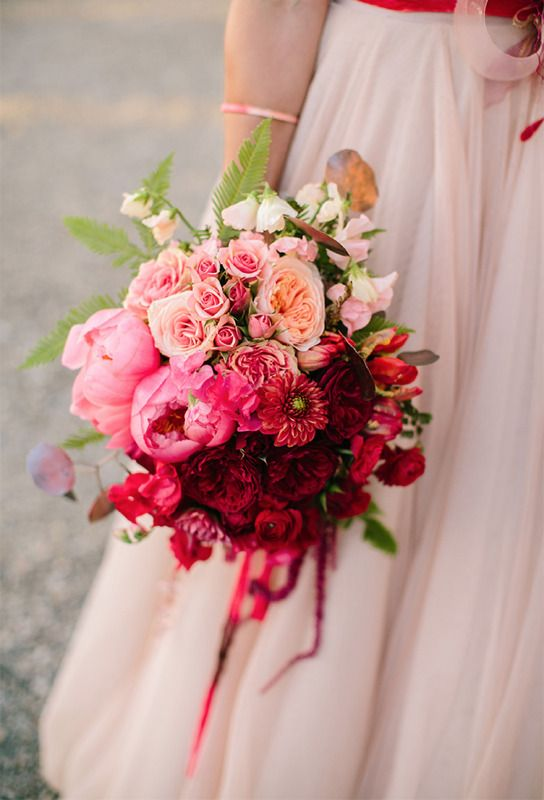 a bold ombre wedding bouquet from blush, lightpink to red and burgundy, with greenery and leaves