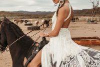 a breathtaking boho lace A-line wedding dress with long fringe, an open back and a front slit for a truly boho bride