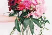 a chic ombre wedding bouquet from burgundy to red, pink and light pink blooms and various greenery