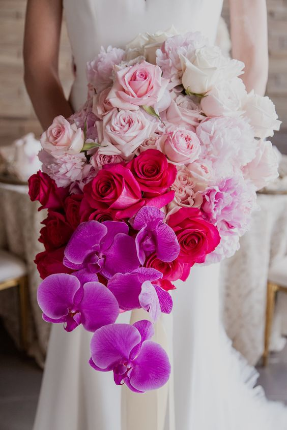 a jaw dropping wedding bouquet from white to light pink, fuchsia and bold purple and a cascading effect is a bright idea