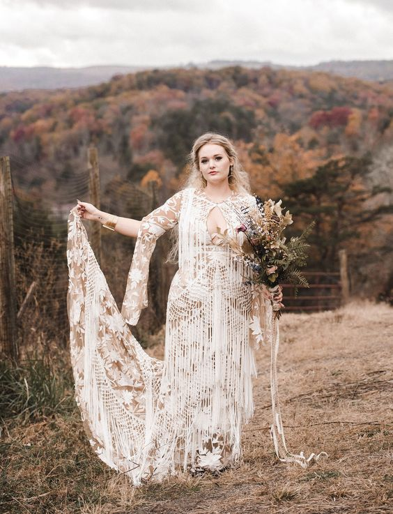 a nude and white boho lace wedding dress with a plunging neckline, long sleeves and lots of fringe covering the dress