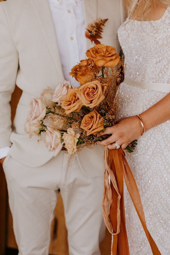 a refined ombre rose wedding bouquet from blush and rust colored blooms, dried herbs and rust colored ribbons