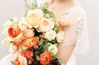 a refined ombre wedding bouquet from peachy to red and orange blooms, with greenery and berries for a fall bride