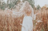 a romantic boho lace A-line wedding dress with a cutout back and long sleeves fully detailed with short wavy fringe