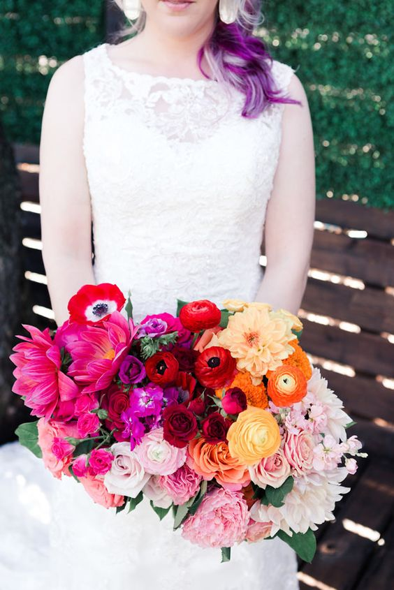 a super bold ombre wedding bouquet of hot pink, pink, blush red, burgundy and orange blooms and of a catchy shape