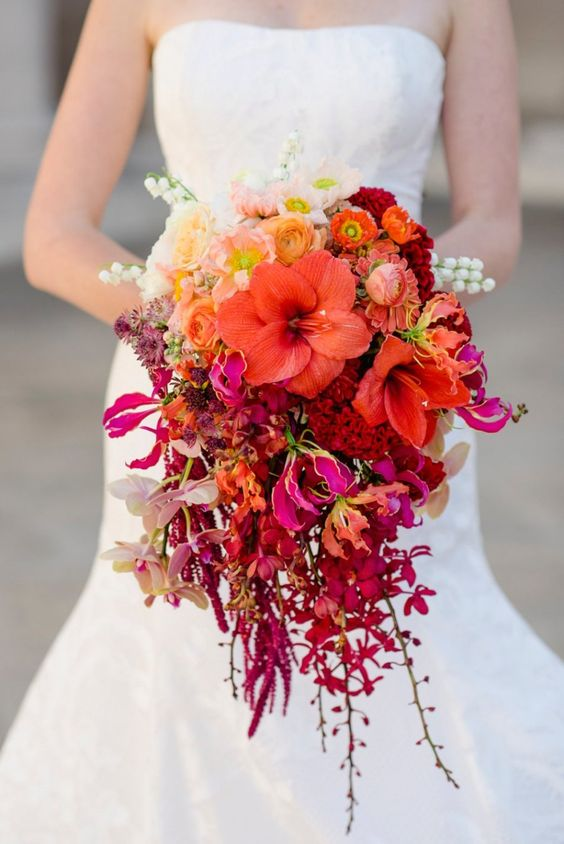a super bright cascading wedding bouquet of blush, orange, red, burgundy and purple blooms and branches hanging