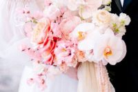 a tender ombre wedding bouquet of blush, light pink and white blooms and pink and white ribbons