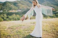 a textural sheath wedding dress with long sleeves detailed with long fringe and a hat for a boho bridal look