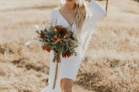 a white plain wedding dress with a high low skirt with a train, a V-neckline, long sleeves with fringe for a boho bride