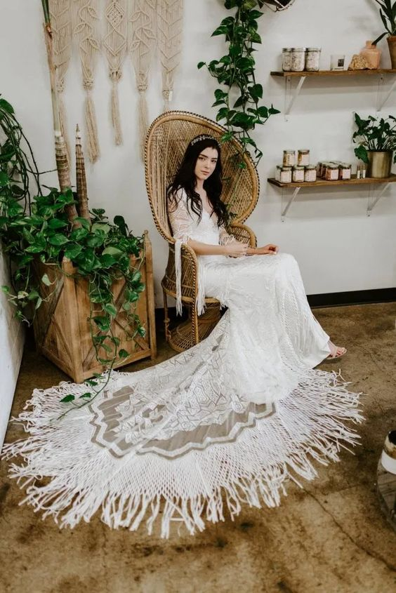 an embellished lace wedding dress with a plunging neckline, short sleeves with fringe and long fringe on the edge of the dress