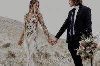 an embroidered floral sheath wedding dress with long sleeves and long fringe on the bodice and sleeves
