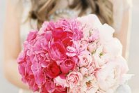 an ombre ball-shaped wedding bouquet from bright pink to red and blush and with pale leaves is a chic and bright idea