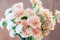 an ombre carnation wedding bouquet from white and blush blooms and some blush ribbons is a stylish and non-traditional idea
