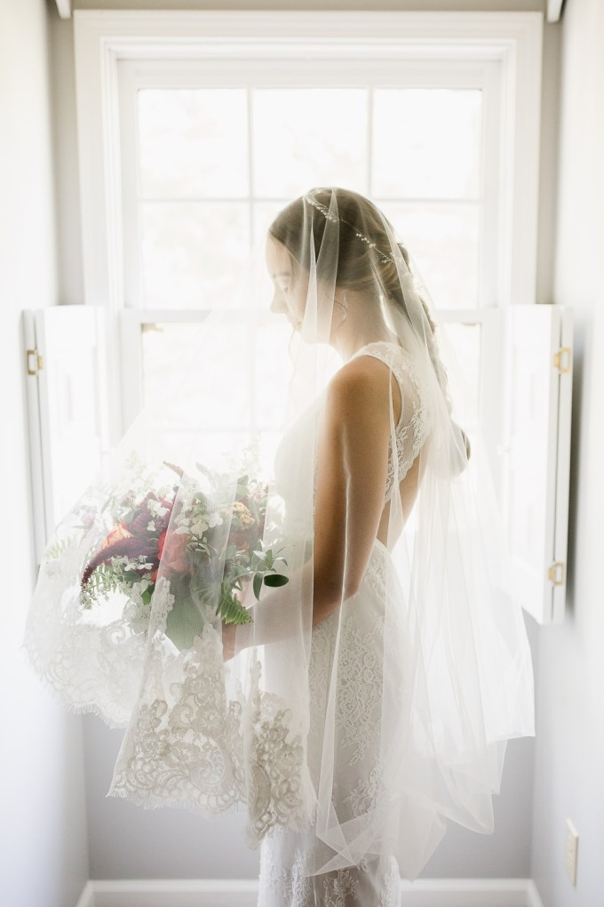 The bride was wearing a lace sheath wedding dress with no sleeves and a keyhole back plsu a veil