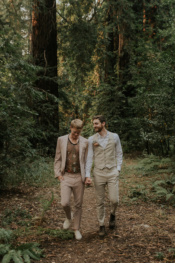 One groom was wearing a tan suit with a sheer floral embroidery top, chains and white moccasins, the other groom was wearing an ivory waistcoat and pants and a floral boutonniere