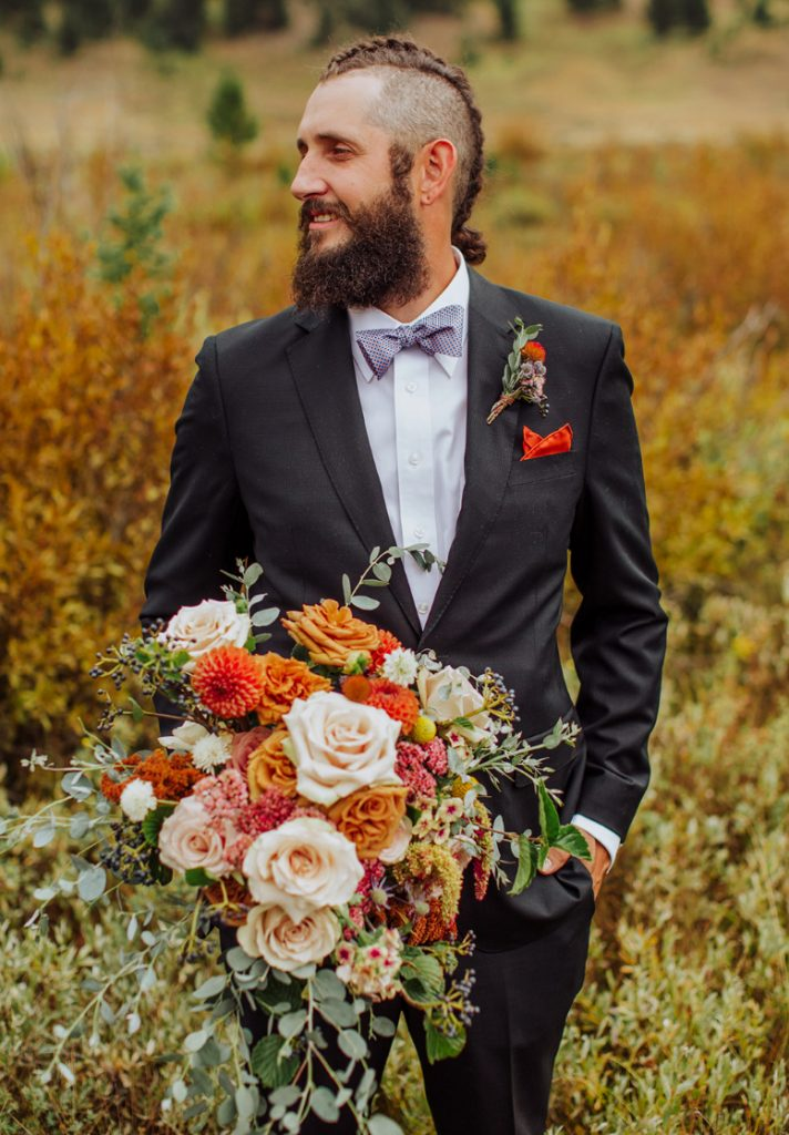 The groom was rocking a black suit, a lavender shirt and a lilac bow tie plus a bold boutonniere