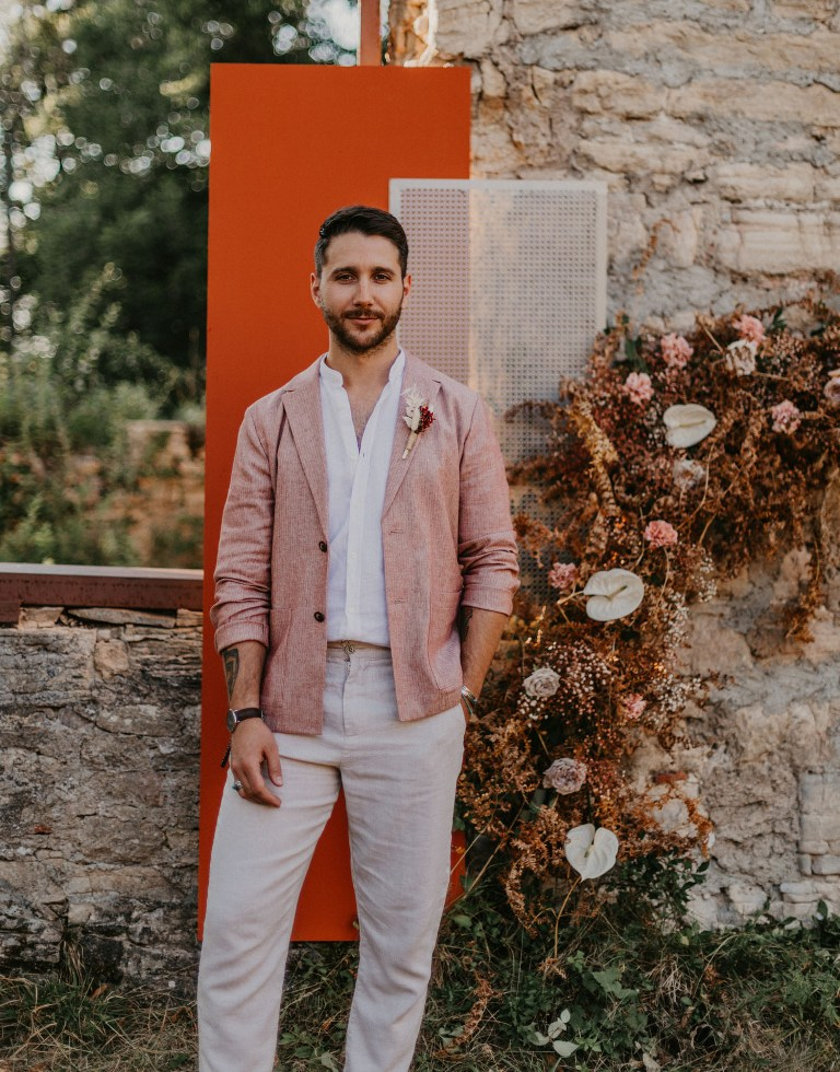 The groom was wearing a terrracotta blazer, a white shirt and pants and brown moccasins