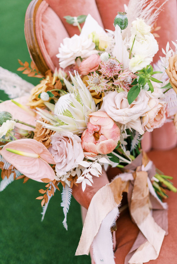 The wedding bouquet was very soft and tender, with blush and white blooms, greenery, pampas grass and blush ribbons