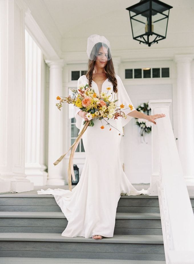 The bride was wearing a plain white wedding dress with a plunging neckline and a train plus a veil