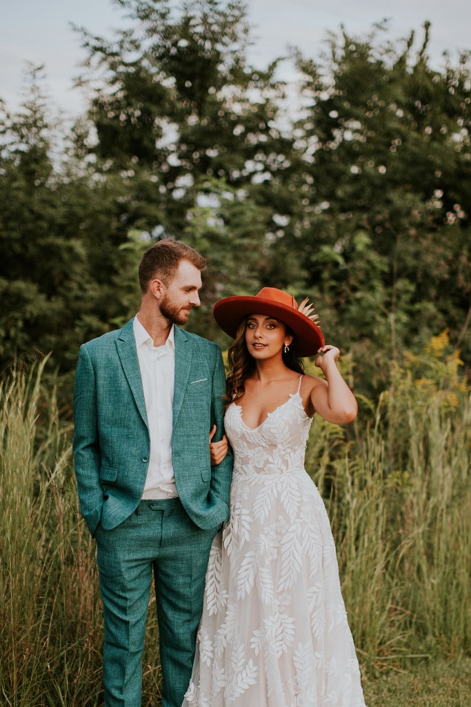 The groom was wearing a teal suit with a white shirt, and the bride was rocking a lace spaghetti strap dress and a red hat