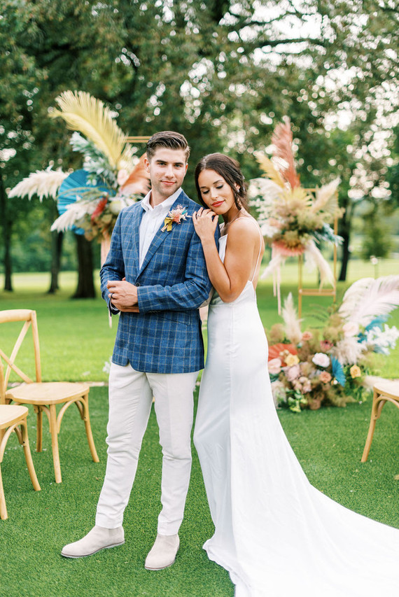 The groom was wearing a white shirt, pants and boots plus a blue plaid blazer, the bride was rocking a classic slip wedding dress with a train