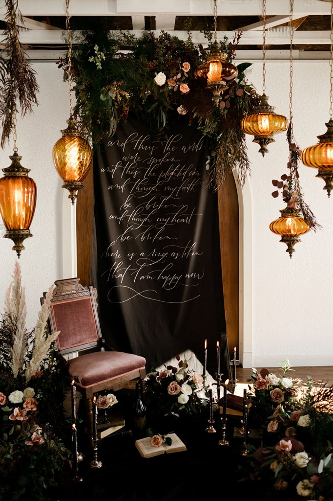 The wedding backdrop was done with a custom banner with Poe quotes, moody florals and greenery, candles and hanging lamps