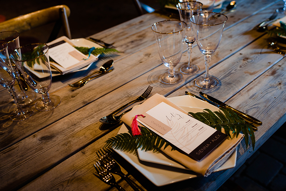 The wedding tablescape was done with an uncovered table, geometric plates and tropical leaves