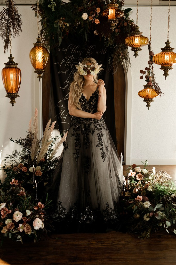 The bride was wearing an A-line wedding dress with black lace appliques and embellishments