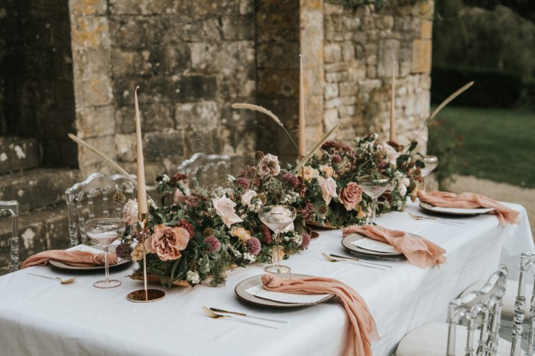 The wedding tablescape was done with peachy napkins, greenery, moss, blush and mauve blooms and candles