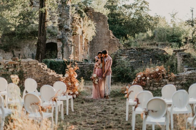 An alternative wedding space - castle ruins decorated with blooms and dried leaves, with white chairs that are very refined