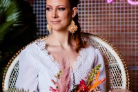 06 The bride was wearing a 70s wedding dress, raffia earrings and a bold hairstyle with blooms plus her piercings