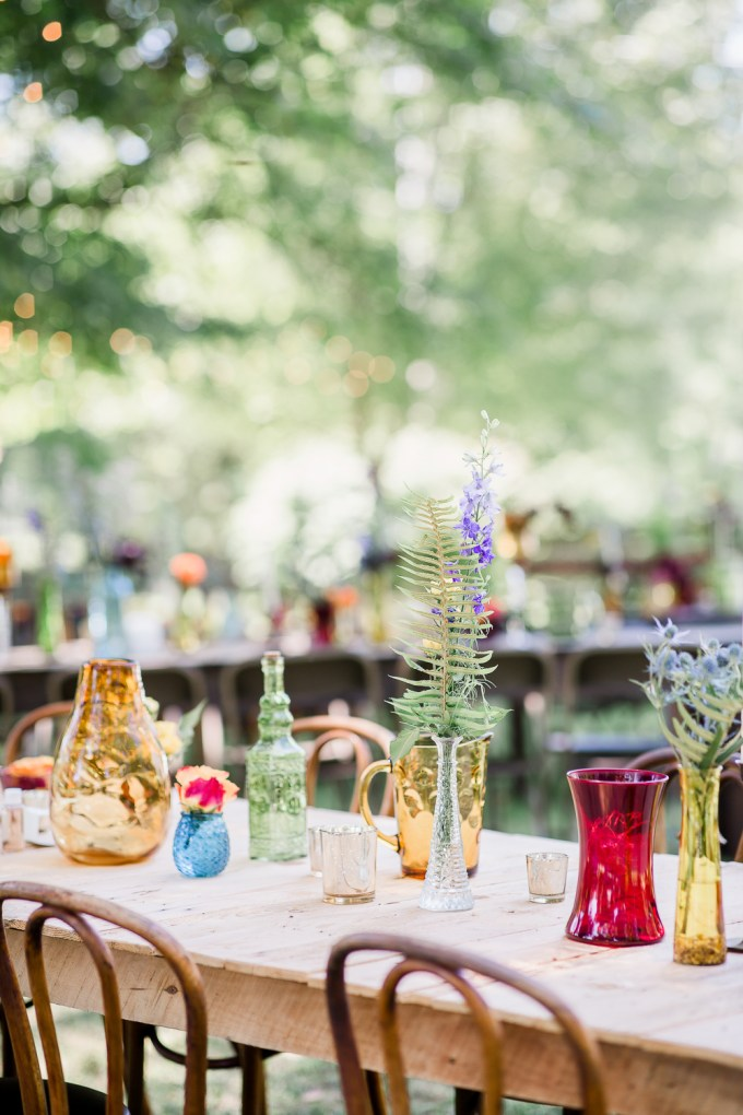 The tablescapes were done with bright mismatching vases and jugs and bold blooms
