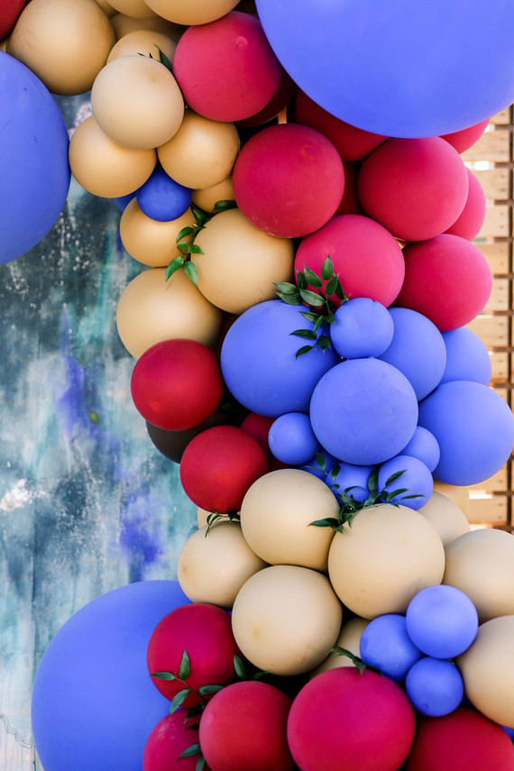 The wedding backdrop was a bold watercolor one with a huge colorful balloon garland and some greenery