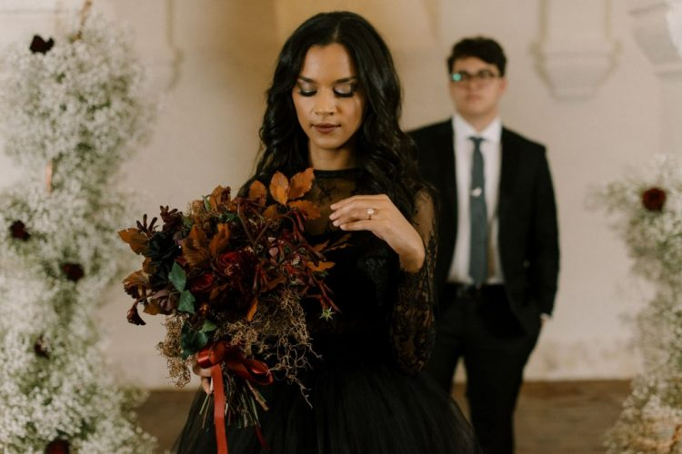 The wedding bouquet was done with dried leaves, dark blooms, moss and herbs plus a red bow
