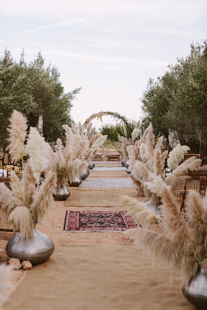 The wedding ceremony space was done with pampas grass in silver vases, burlap and boho rugs and a greenery and pampas grass arch