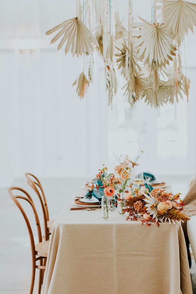 The wedding tablescape was done with terracotta and peachy blooms andd teal linens plus dried fronds over it