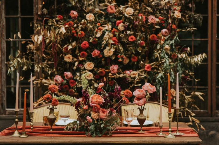 The wedding tablescape was done with the same bold flal colored blooms and greenery, colorful candles and bold linens