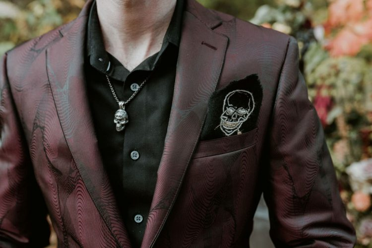 The groom was wearing a black shirt, a printed burgundy blazer and some skulls here and there