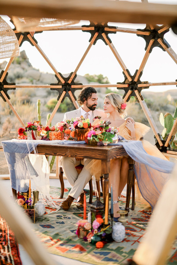 The reception table was done with a breezy runner, bold blooms and fruits and some bright candles and cacti