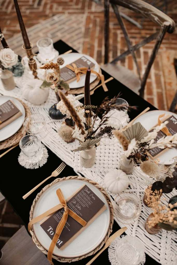 The wedding tablescape was done with a macrame runner, woven chargers, white porcelain, pumpkins and dried herbs and blooms