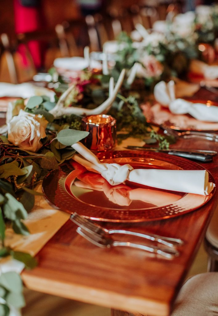 The wedding tablescapes were done with greenery and blush rose runners and antlers, copper mugs and chargers and white napkins