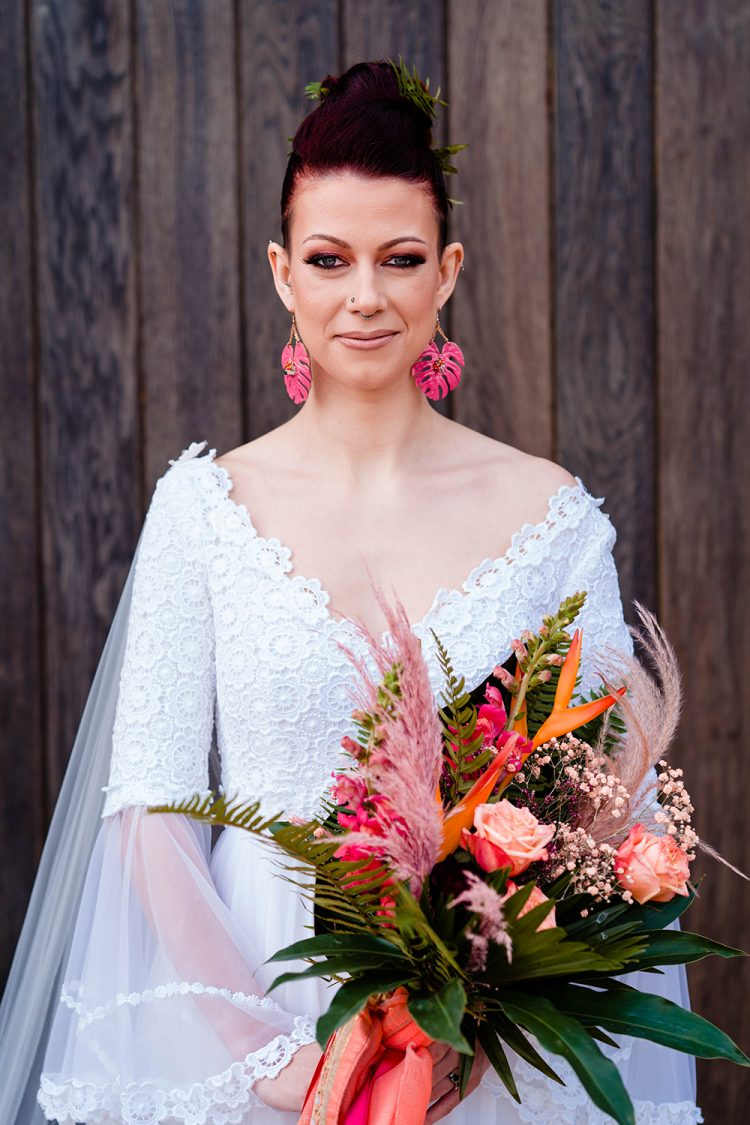 The wedding bouquet was done with pink, blush and orange blooms, leaves and pink pampas grass