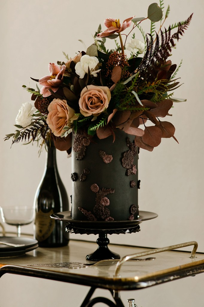 The wedding cake was done black and accented with dark sugar blooms, moody blooms and greenery on top